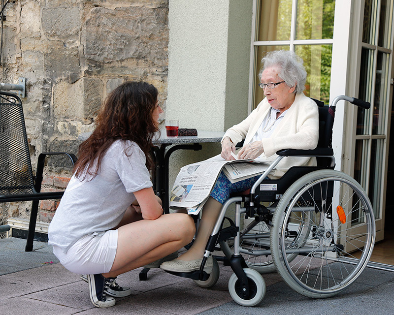 Betreuerin mit Seniorin im Rollstuhl