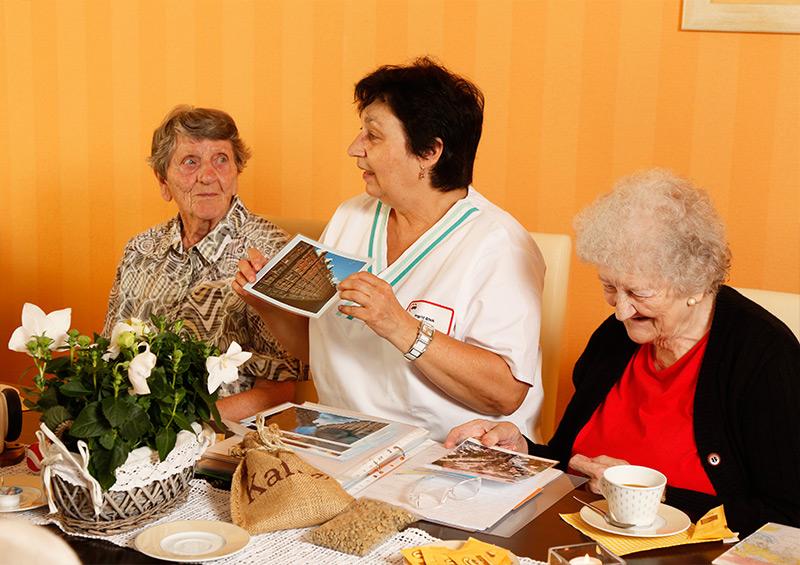 Pflegerin zeigt einer Gruppe von Senioren Bilder