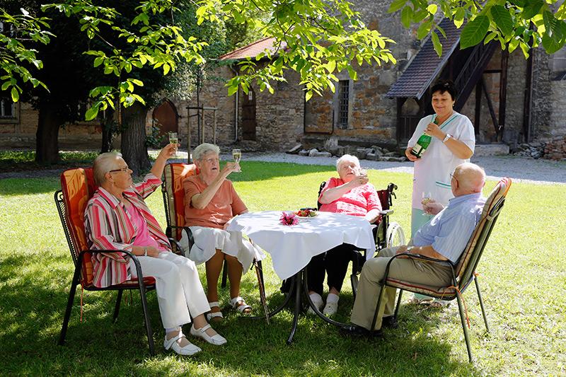 Senioren sitzen im Garten