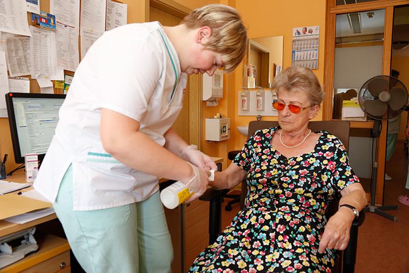 Pflegefachkraft desinfiziert den Arm einer Seniorin