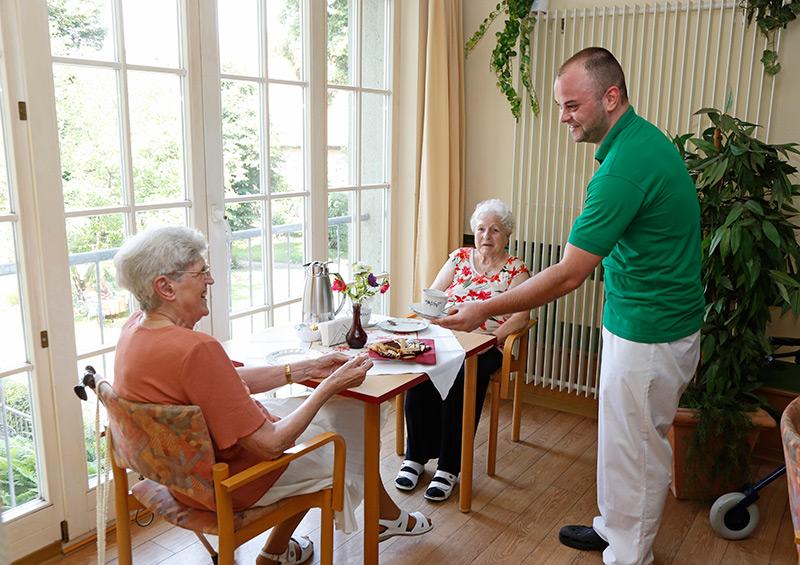 Ein Pfleger serviert einer Seniorin eine Tasse Kaffee